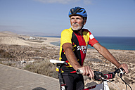 Spain, Canary Islands, Fuerteventura, senior man with mountainbike having a rest - MFRF00846