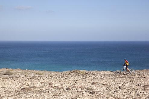 Spain, Canary Islands, Fuerteventura, senior man on mountainbike - MFRF00852