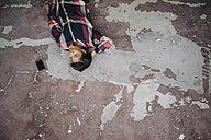 Woman lying on cracked floor with cell phone - KNSF01518