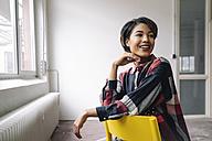 Smiling woman sitting on chair - KNSF01524
