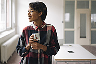 Smiling young woman holding cup - KNSF01527