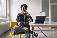 Confident young woman sitting on chair with laptop on table - KNSF01533