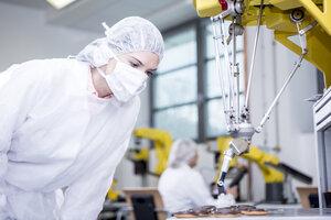 Woman in factory examining robot handling cookies - WESTF23401