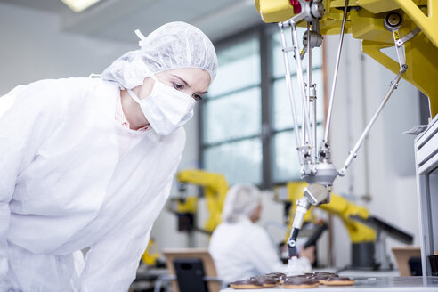 Woman in factory examining robot handling cookies - WESTF23401