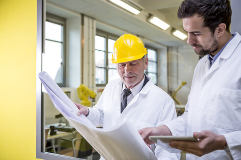 Two engineers in factory looking at plan - WESTF23404
