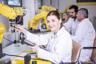 Portrait of smiling engineer examining industrial robot - WESTF23407