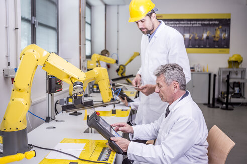 Two engineers in factory looking at device - WESTF23410