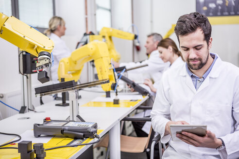 Engineer using tablet in factory with industrial robots - WESTF23413