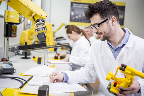 Engineer in factory holding model of an industrial robot taking notes on clipboard - WESTF23419