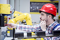 Man wearing hard hat adjusting industrial robot - WESTF23422