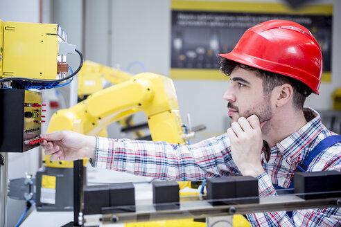 Man wearing hard hat adjusting industrial robot - WESTF23422