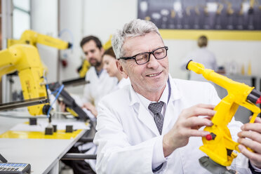 Engineer holding model of an industrial robot - WESTF23425