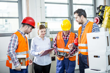 Staff discussing in factory with industrial robot in background - WESTF23431