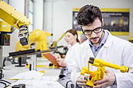 Engineer holding model of an industrial robot - WESTF23437