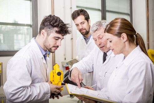 Engineers with industrial robot model checking documents - WESTF23440