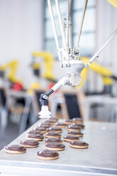 Close-up of industrial robot handling cookies - WESTF23449
