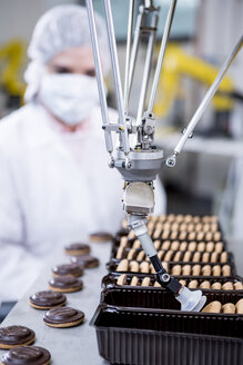 Woman in factory looking at robot handling cookies - WESTF23452