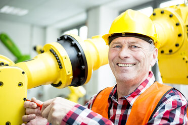 Portrait of smiling technician working on industrial robot - WESTF23464