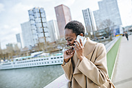 France, Paris,  Young businesswoman talking on the phone - KIJF01544
