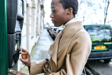 France, Paris, Young woman paying with her smartphone at parking automat - KIJF01547