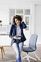 Businesswoman in office sitting on desk, using digital tablet - KNSF01552