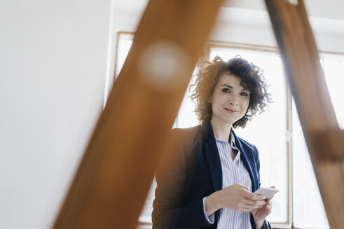 Businesswoman standing by ladder in office, holding smartphone - KNSF01558