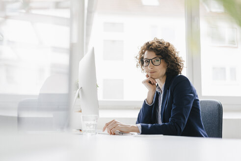 Businesswoman in office sitting at desk - KNSF01564
