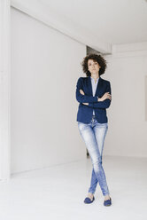 Businesswoman standing in loft with arms crossed - KNSF01573