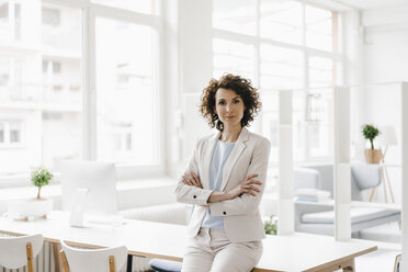 Businesswoman in office sitting on desk with arms crossed - KNSF01600