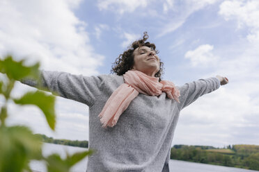 Woman standing at lake pretending to fly - KNSF01615