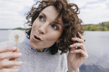 Woman at lake holding blowball - KNSF01624