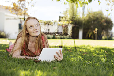 Grl with long red hair lying in grass with tablet - ZEF13930