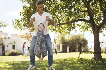 Father playing with daughter in grass - ZEF13933