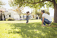 Father and daughter with hula hoops in grass - ZEF13936