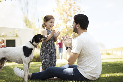 Happy father, daughter and dog in garden - ZEF13939