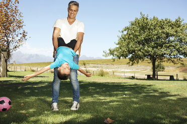 Father playing with son in garden - ZEF13951