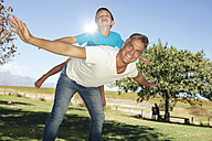 Father playing with son in garden - ZEF13954
