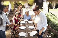 Family setting table outside for lunch - ZEF13966