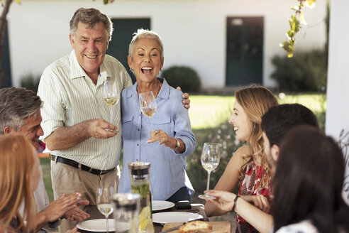 Happy senior couple with family having lunch together outside - ZEF13972