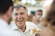 Happy senior man socializing on a garden party - ZEF13981