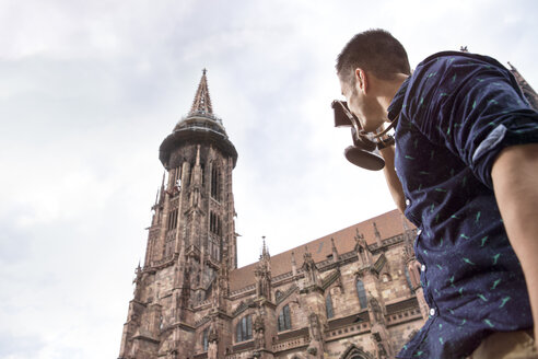 Germany, Freiburg, young man taking a picture of the minster - MIDF00841