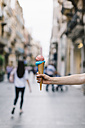 Close-up of woman holding ice cream conein shopping street - JPF00215