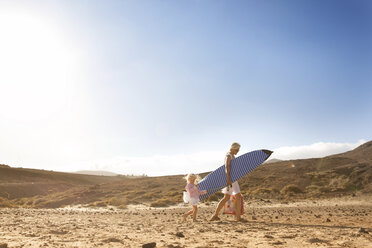 Spain, Fuerteventura, mother and daughter walking with surfboard on the beach - MFRF00857