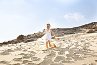 Spain, Fuerteventura, girl running down dune on the beach - MFRF00863