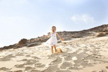 Spain, Fuerteventura, girl running down dune on the beach - MFRF00863