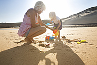 Spain, Fuerteventura, mother and daughter playing on the beach - MFRF00869