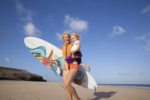 Spain, Fuerteventura, happy mother and daughter walking with surfboard on the beach - MFRF00872