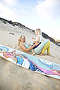 Spain, Fuerteventura, happy mother and daughter on the beach next to surfboard - MFRF00875