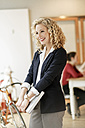 Portrait of smiling businesswoman with a meeting in background - PESF00641