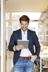 Smiling businessman using tablet in office - PESF00650